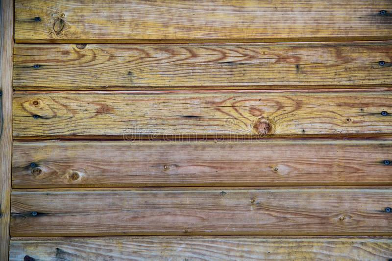 Background of old boards yellow and purple with knots hammered nails. Design backgrounds texture stock images
