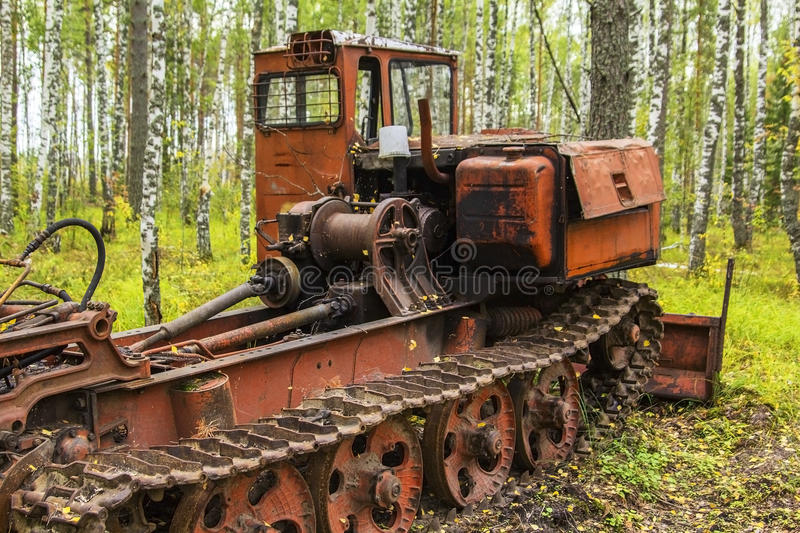 Background old rusty abandoned tractor standing in the woods. Background old rusty abandoned orange tractor standing in the woods stock images