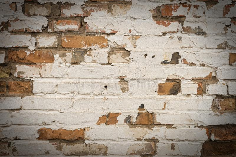 Background of old vintage dirty brick wall with peeling plaster, texture. royalty free stock photography