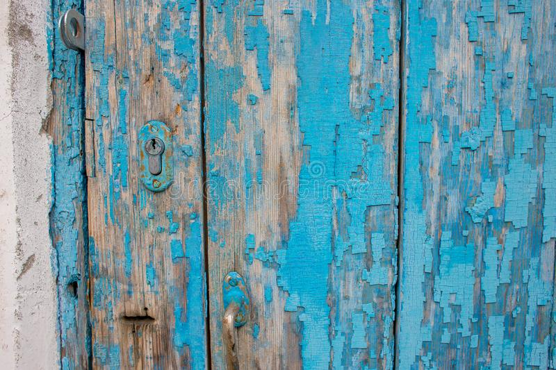 Part of an old wooden door with peeling blue paint and a keyhole. Background from an old wooden door painted in blue. Texture of peeling paint on the boards stock photography