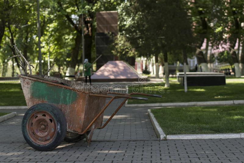 A shabby metal wheelbarrow for garbage disposal in the park. In the background out of focus, a janitor is manually sweeping a walkway in a park. In the stock images