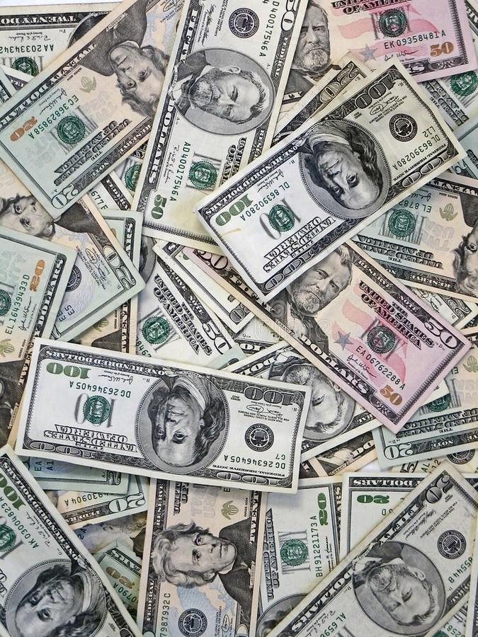 Background from paper dollars of different advantage. Dollars background. Many 20, 50, 100 dollar bills stock images