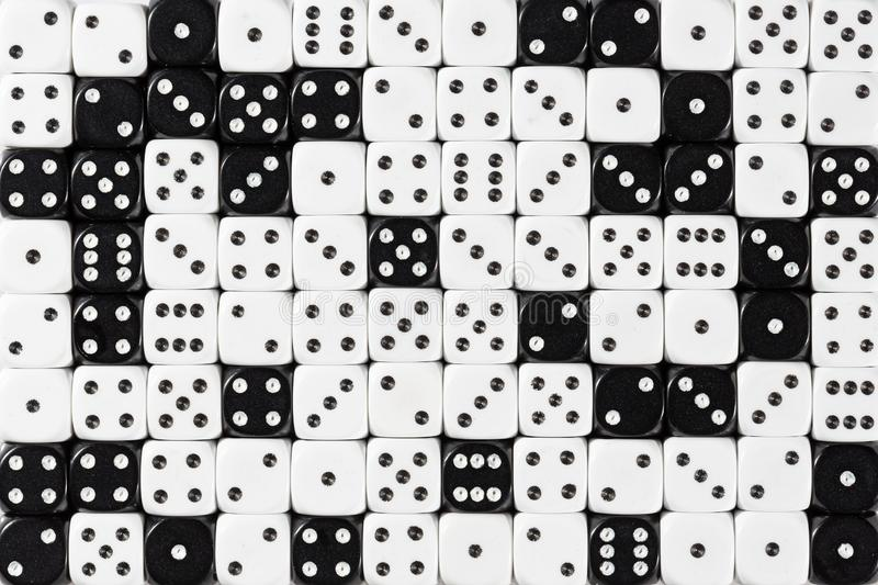 Background patteren of random ordered white and black dices. Pattern background with two-third random ordered white dices and one-third black dices stock photo