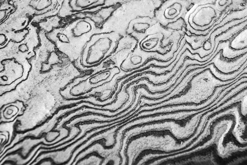 Background with pattern of damask steel. Close up. Macro shot of a damascus knife blade texture. Damascus steel pattern. Metal and stock photography