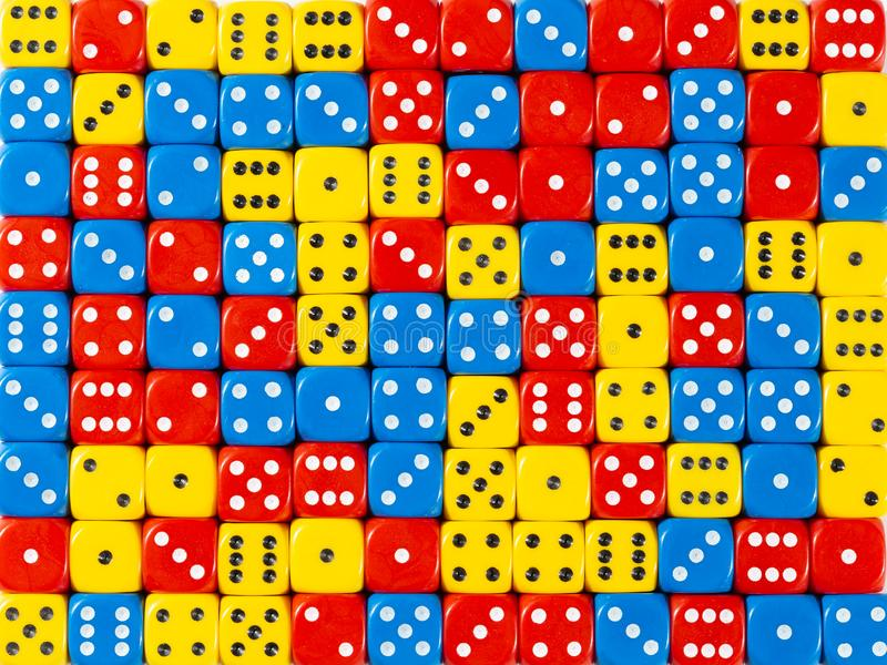 Background pattern of random ordered red, blue and yellow dices. Pattern background of random ordered red, blue and yellow dices stock photo