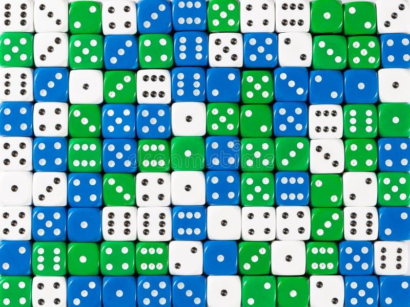 Background pattern of random ordered white, blue and green dices. Pattern background of random ordered white, blue and green dices royalty free stock image