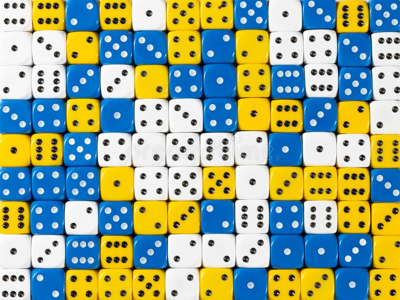 Background pattern of random ordered white, blue and yellow dices. Pattern background of random ordered white, blue and yellow dices stock images