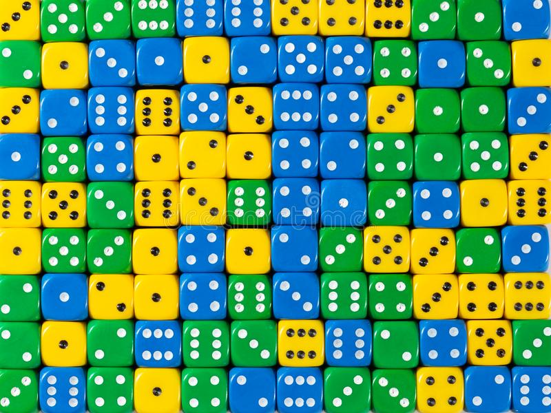 Background pattern of random ordered yellow, green and blue dices. Pattern background of random ordered yellow, green and blue dices stock photography