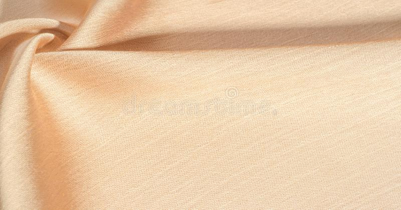 Background, pattern, texture, beige golden silk fabric It has a smooth matte finish and is durable due to a slightly twisted yarn. stock photo