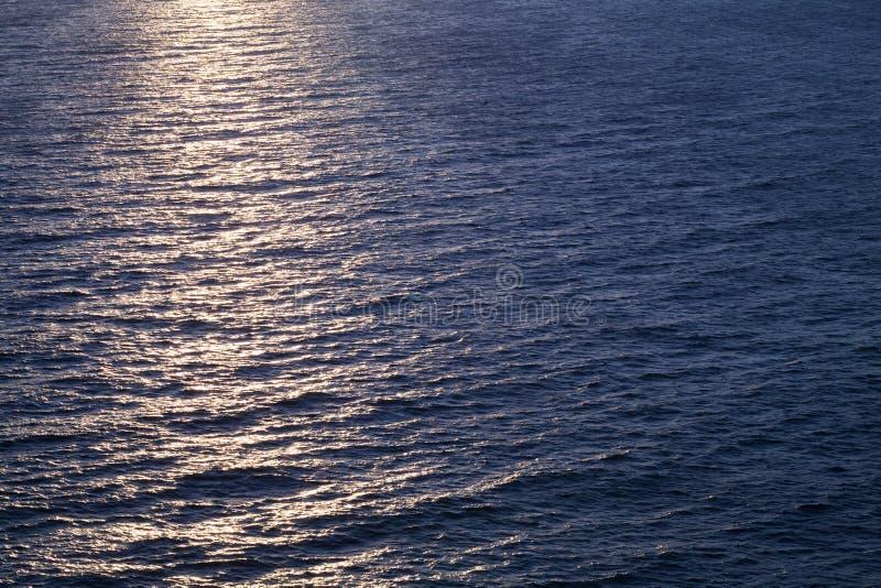 Background photo, sun glare on dark sea water stock photo
