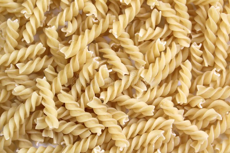 Texture of pasta in the form of a spiral. Background picture, beauty, closeup, concoction, cuisine, diet, dinner, dry, eat, food, fresh, golden, useful stock photos