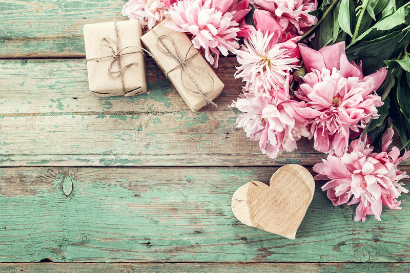 Background with pink peonies, gift box and a wooden heart on old stock photos