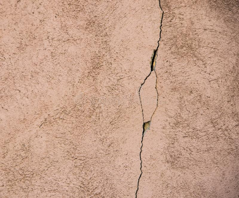Background of pinkish rough stucco with a vertical crack stock photography