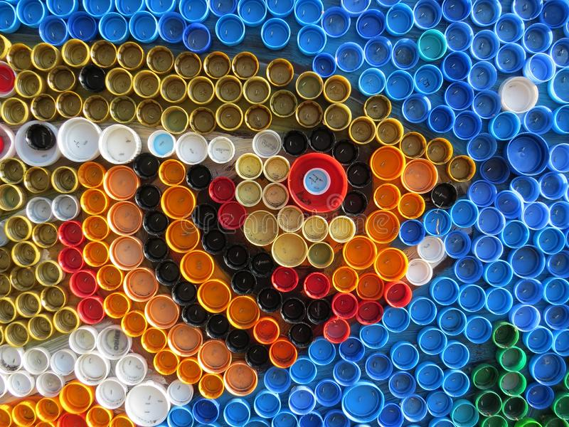 Background of plastic colorful bottle caps. Contamination with plastic waste. Environment and ecological balance. Art from junk. Festive and fun colored mosaic royalty free stock image