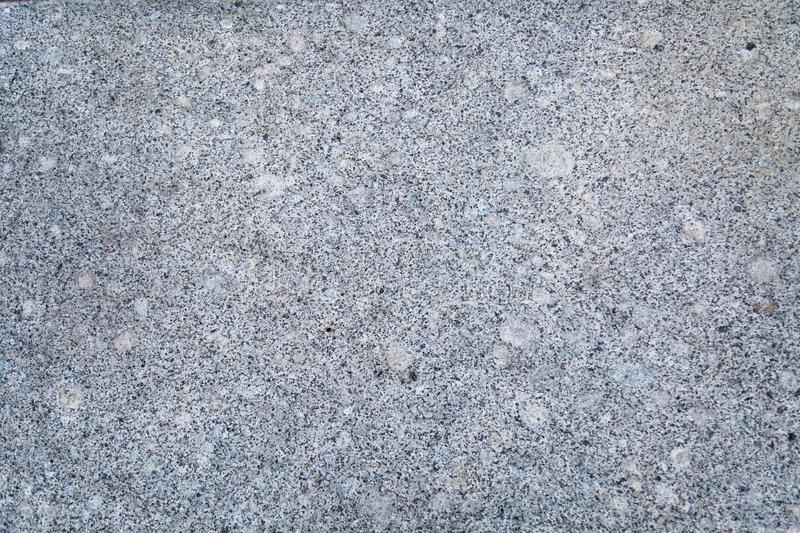 Background of polished granite white smoky color with lilac black specks. royalty free stock image