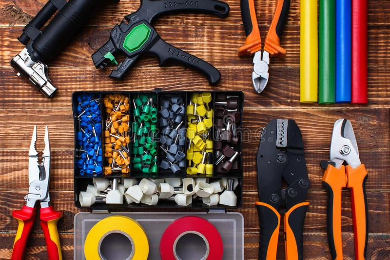 Background of professional electrician tools: cable lugs in the organizer box, insulating tape, earplugs, cutters, tips, burnerpul royalty free stock image