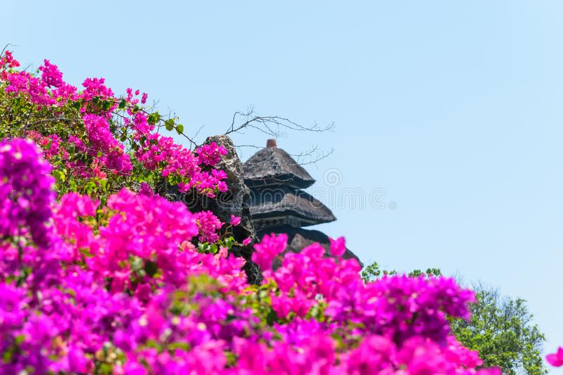 Background of purple blooming flowers and traditional Bali temple roof. Flowers foreground and roof are blurred. Main camera focus is the rock stock photo