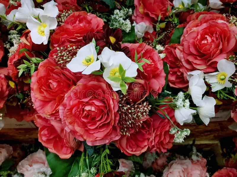 Background of Red Artificial Roses and Other White Flowers with Selective Focus stock image