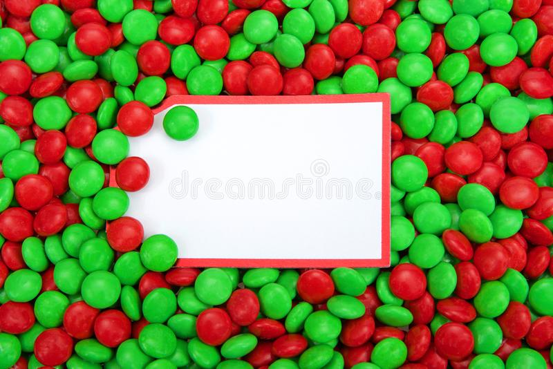 Background of red and green candy coated chocolates with blank note card in the middle for text royalty free stock image