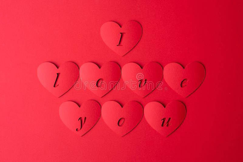 The background is red, the red hearts are cut out of paper with the words I love you. Valentine`s day pattern royalty free stock photography