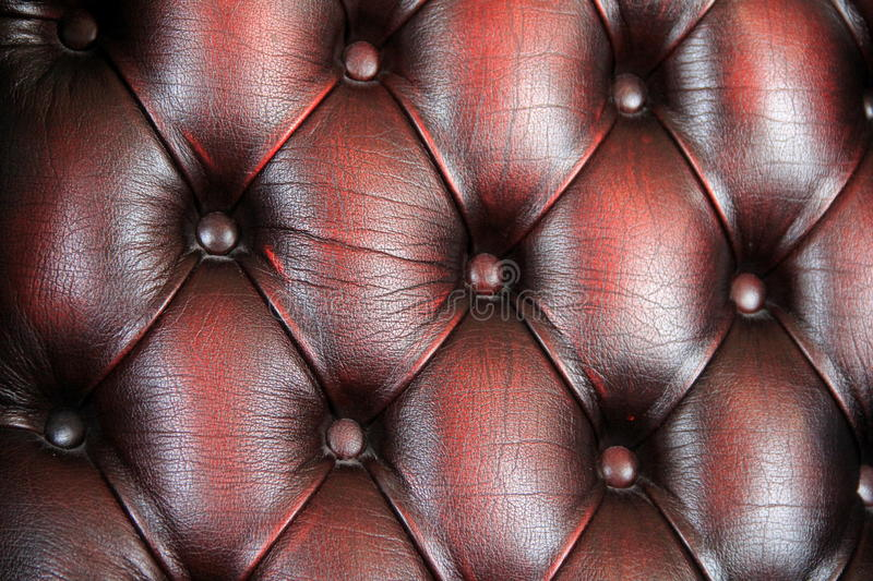 Background of rich burgundy colored leather and buttons. Detail in background of rich tones of burgundy color leather chair and buttons that hold the diamond stock images