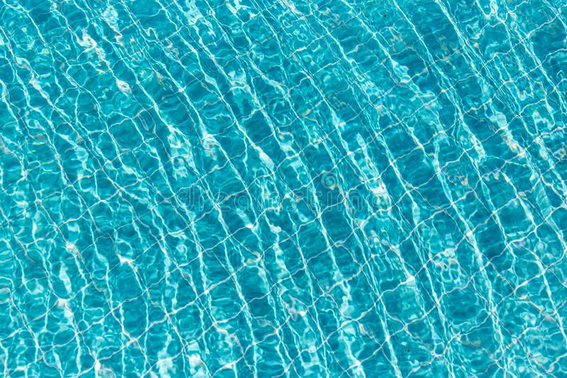 Background of rippled pattern of clean water in a blue swimming pool. Abstract, aqua, bright, clear, cool, fresh, light, liquid, nature, ocean, pure royalty free stock images