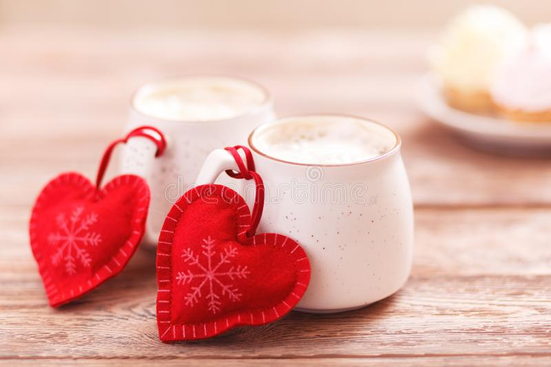Two cups of coffee with a heart for Valentine`s Day, birthday, Christmas. Wooden background. Cakes on blurred background. Background romantic mood. Two cups of stock photo