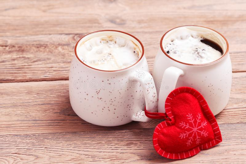 Two cups of coffee with decorative felt heart on wooden background close-up. The Concept Of Valentine`s Day, Christmas stock images