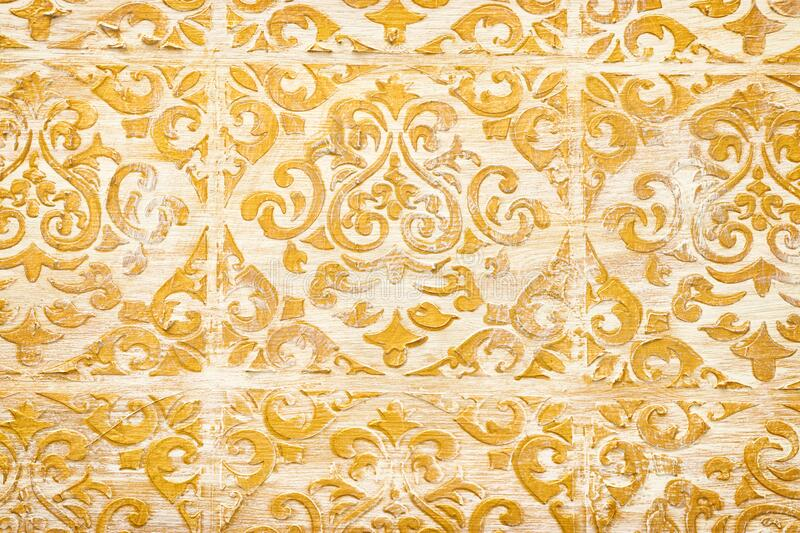 Background of royal gold wooden vintage background with floral emboss details.  stock image