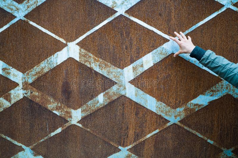 Background of rusted vintage metal with a diamond pattern and vintage blue paint and a slender open female hand stock photos