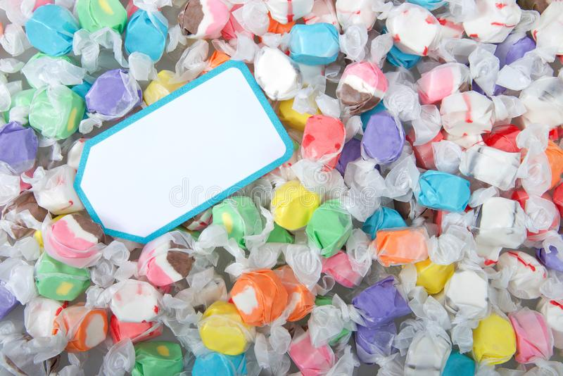 Background of salt water taffy in various flavors and colors with blank note card royalty free stock image