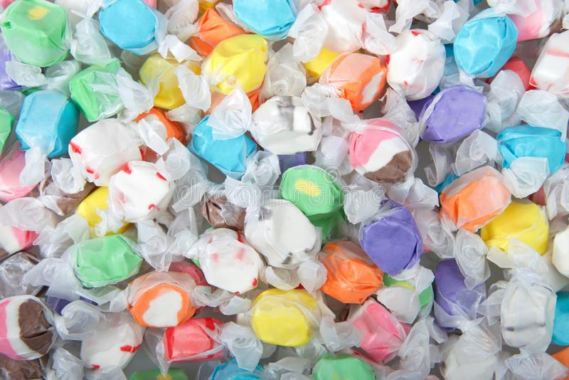 Background of salt water taffy in various flavors and colors. Wrapped in white transparent paper. Salt water taffy is sold widely on the boardwalks in the U.S stock photos