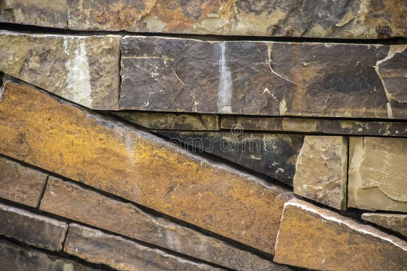 Background of sandstone rocks stacked with some on a diagonal and some horizontal - variety of colors and textures.  royalty free stock photo
