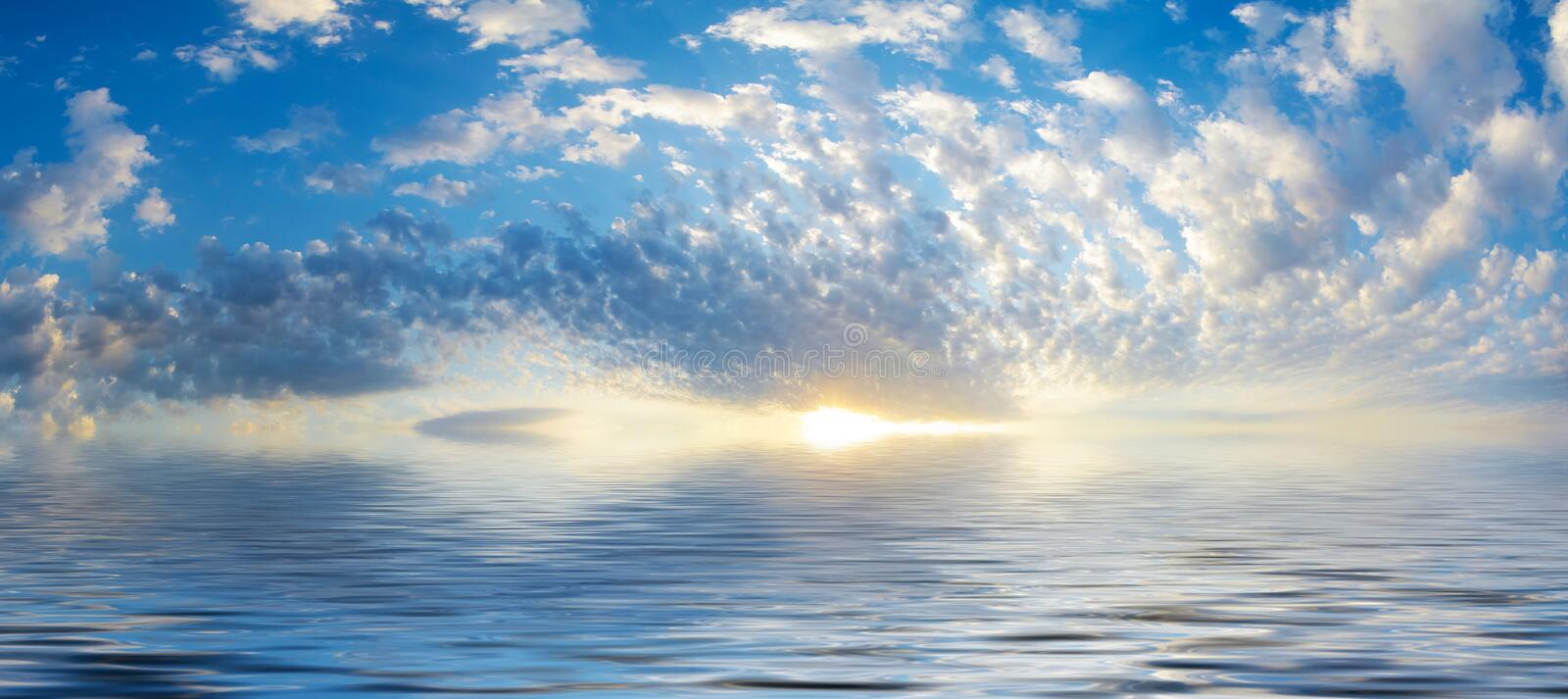 Background of seascape with rising sun. Summer sky with rising sun above calm water.Seascape with beautiful reflection white clouds in sunny weather stock images