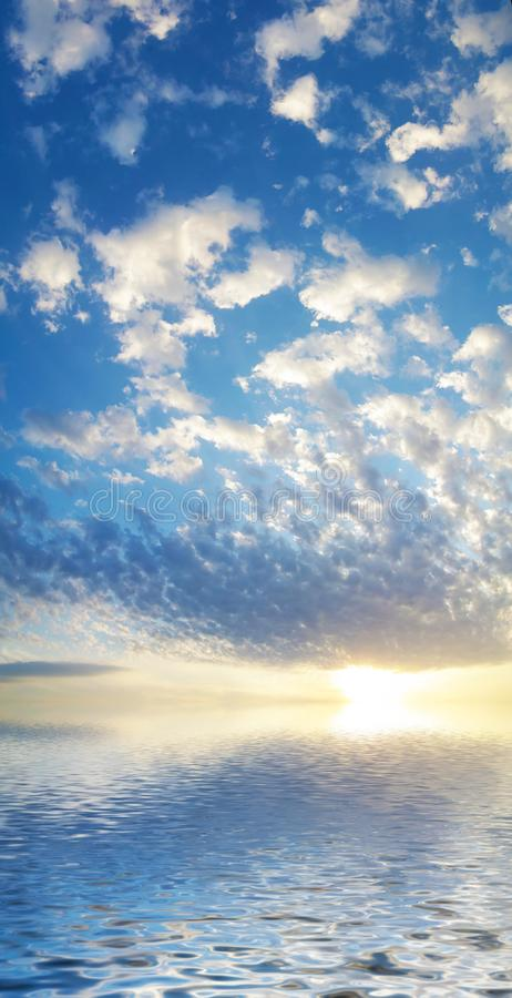 Background of seascape with rising sun. Summer sky with rising sun above calm water.Seascape with beautiful reflection white clouds in sunny weather royalty free stock photos