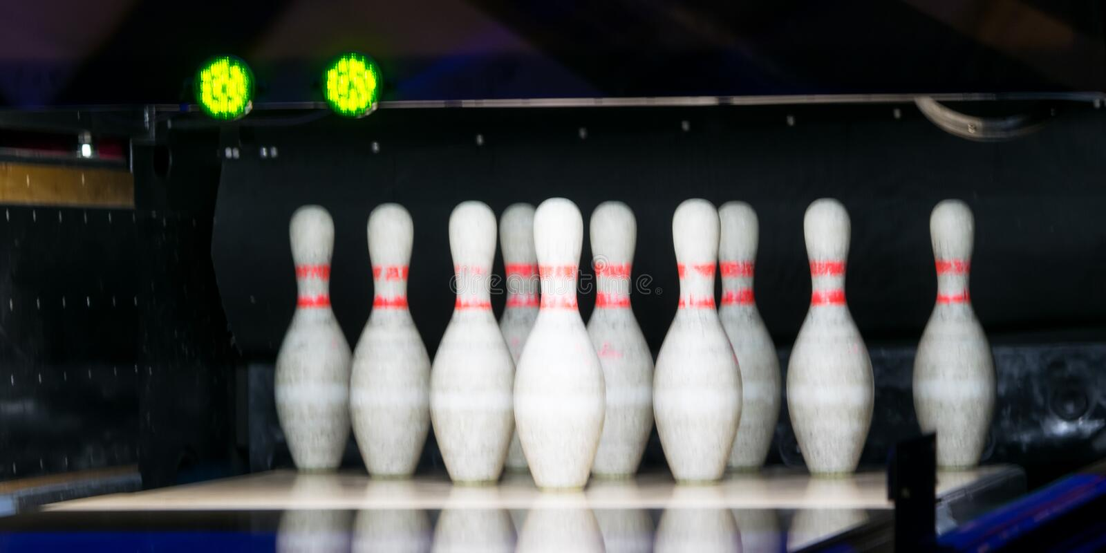 Background, a set of pins are to hit them with a ball, the traffic light is green stock photos