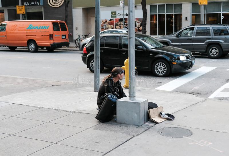 Homeless man seen sitting by the side of a road crossing in a busy city. stock photos