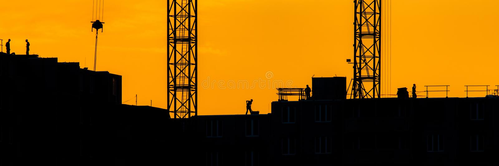 Background of silhouette building crane lift loads with sun set rays yellow cloudy evening sky backdrop Construction site at stock photography