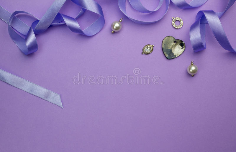 Background with silver, crystal, pearl and charms and heart moth. Er of pearl pendant isolated on purple withsatin ribbon as frame at top - Mothers day royalty free stock photography