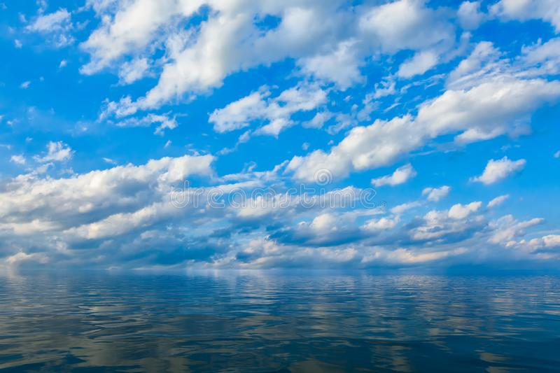 Background of sky with clouds reflected in water or ocean stock image