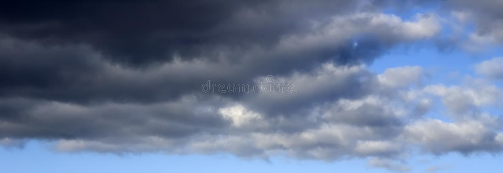 Background sky in the evening. Dramatic alarming colors before sunset with black and grey clouds on blue sky royalty free stock image
