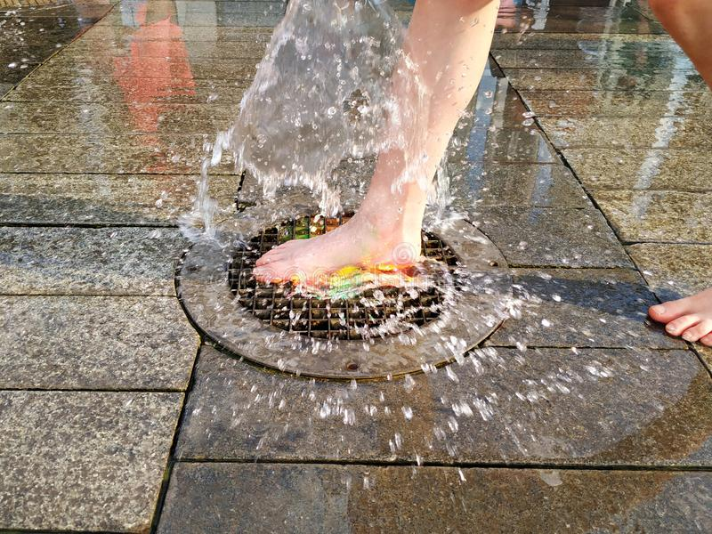 The child`s feet jump on the fountain. A jet of water rises from the surface of the iron lattice. Spray flying in all directions. On the background of stone stock images