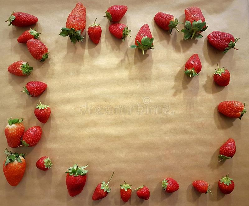 Background of strawberries for greetings and blessings: anniversaries, Valentine`s Day, birthdays, restaurant, love, friendship. Strawberry frame royalty free stock image