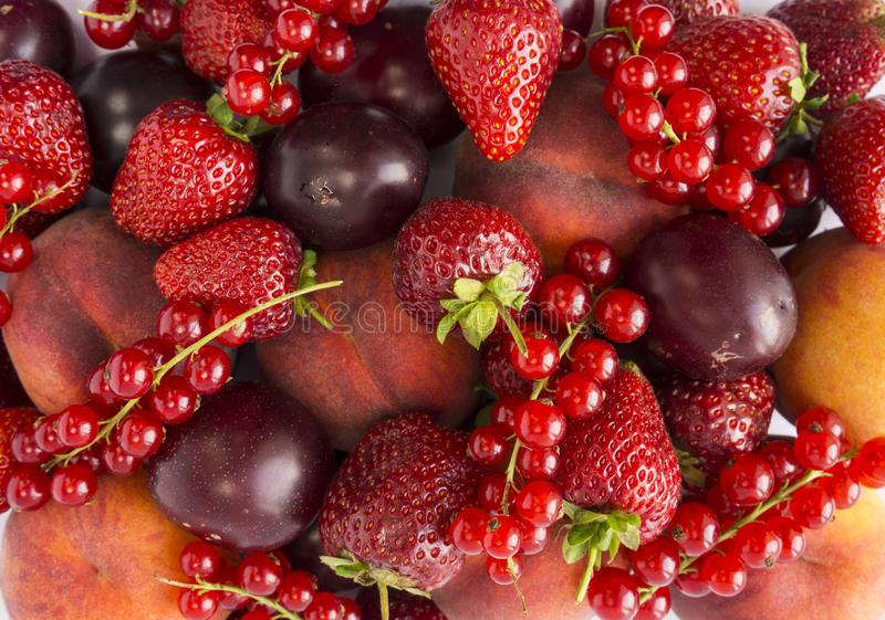 Background of strawberries, peaches, red currants and plums. Fresh berries closeup. Top view. Background of red berries. Various f stock images