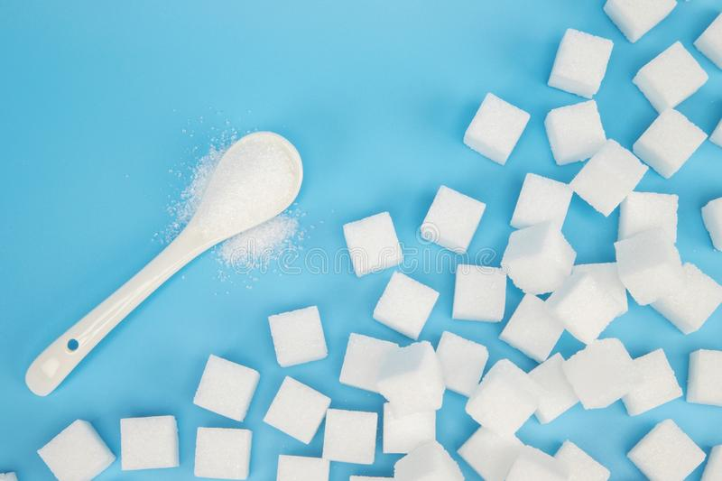 Background of sugar cubes. Sugar with copy space. White sugar on turquoise. Blue background. soft focus stock image