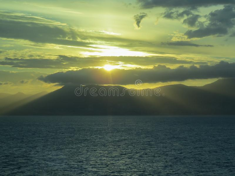 Background. Sunset. Sea and mountains. The sun`s rays make their way through the clouds royalty free stock photo