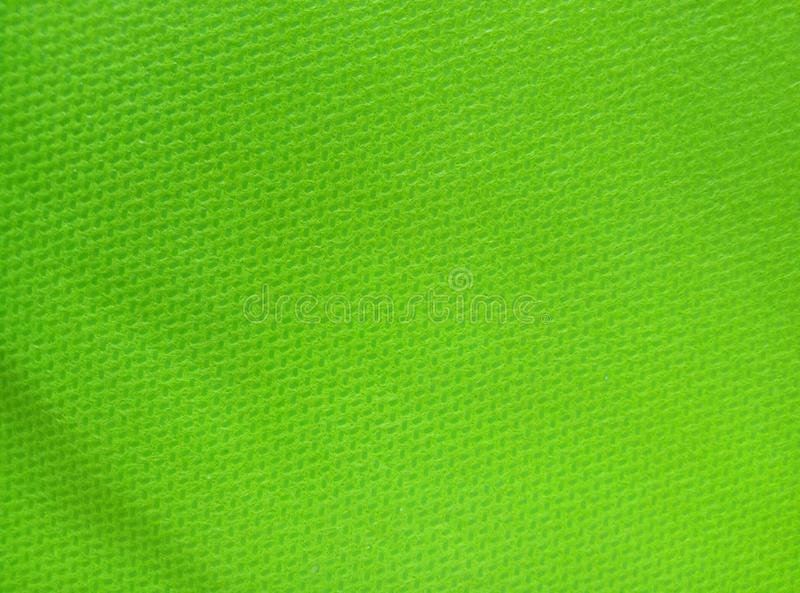 The background surface of the bright green canvas fabric. Bag, material, cloth, fiber, hollow, macro, porous, textured, area, blank, color, detail, fibre royalty free stock images