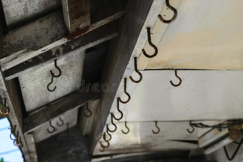 Background surface of old and rusty hooks hanging on the roof stock photography