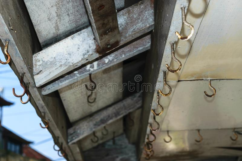Background surface of old and rusty hooks hanging on the roof of shop stock photos