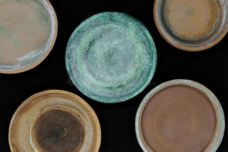 Background surface of various colors and dirty clay plates for plants and isolated on black background.  stock photography